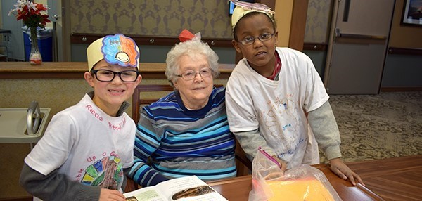 Two Glenwood Elementary second-grade boys visit with a resident at Vestal Park Nursing and Rehabilitation after presenting two Readers Theaters with their classes on December 18, 2018.