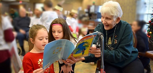 Two second-graders from Glenwood Elementary School read to a Vestal Park Nursing and Rehabilitation resident after their Readers Theater presentation on December 18, 2018.