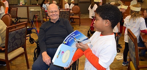 A second-grade boy from Glenwood Elementary holds open the page of a book he is reading to a Vestal Park resident to show him the picture in the book. After a Readers Theater presentation on December 18, 2018.
