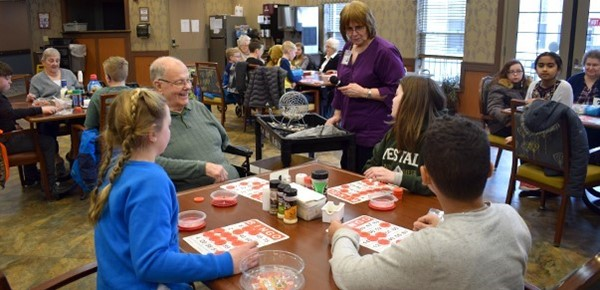 A Vestal Park resident in wheelchair smiles as one of his three table mates, all Glenwood Elementary School students, gets Bingo during a game in one of the facility's dining rooms on February 25, 2019.