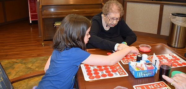 A Glenwood Elementary girl puts a red disk on a Vestal Park resident's Bingo card during a game in the facility's dining hall on February 25, 2019.