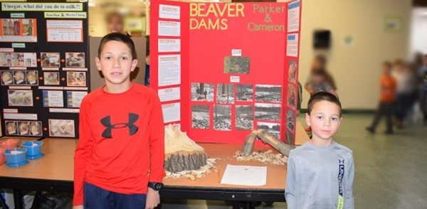 Two brothers, one in fourth grade and one in Kindergarten, pose next to their Science Fair display about Beaver Dams in the African Road Elementary School cafeteria on March 6, 2019.