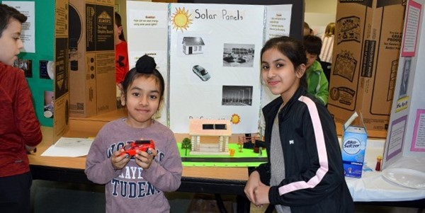An African Road Elementary first-grader stands next to his Science Fair collaborator, a fifth-grader, in front of their project about the energy-saving properties of solar energy in the school cafeteria on March 6, 2019.