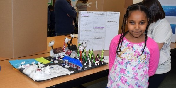 An African Road Elementary third-grade girl poses next to the diorama she constructed to demonstrate the different types of pollution at the Science Fair preview on March 6, 2019.