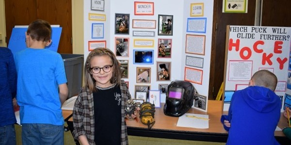 An African Road Elementary first-grade students holds a metal hedgehog she created with her father's help as part of her Science Fair project on welding.