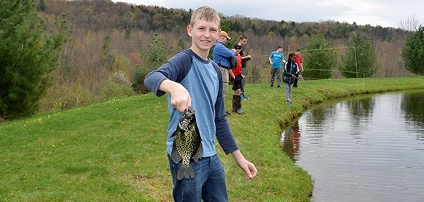 A Vestal Middle School boy holds a large fish he just pulled out of Van Gorder's pond on May 3, 2019, as he and the rest of his friends enjoy their last day of the fly-fishing student activity club.