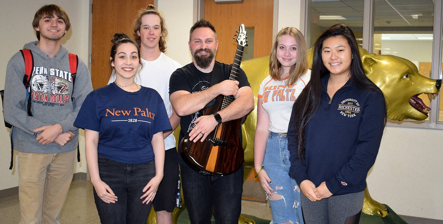 With guitar in hand, Mr. Jared Campbell poses for a photo with five music students in front of the G