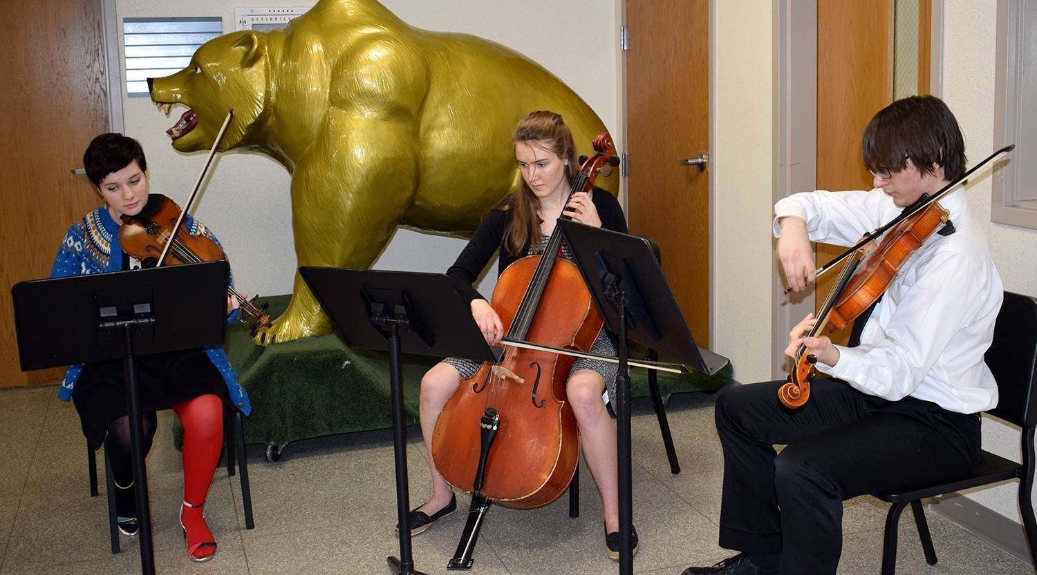A string trio of student musicians play in the Vestal High School lobby during the social hour prece
