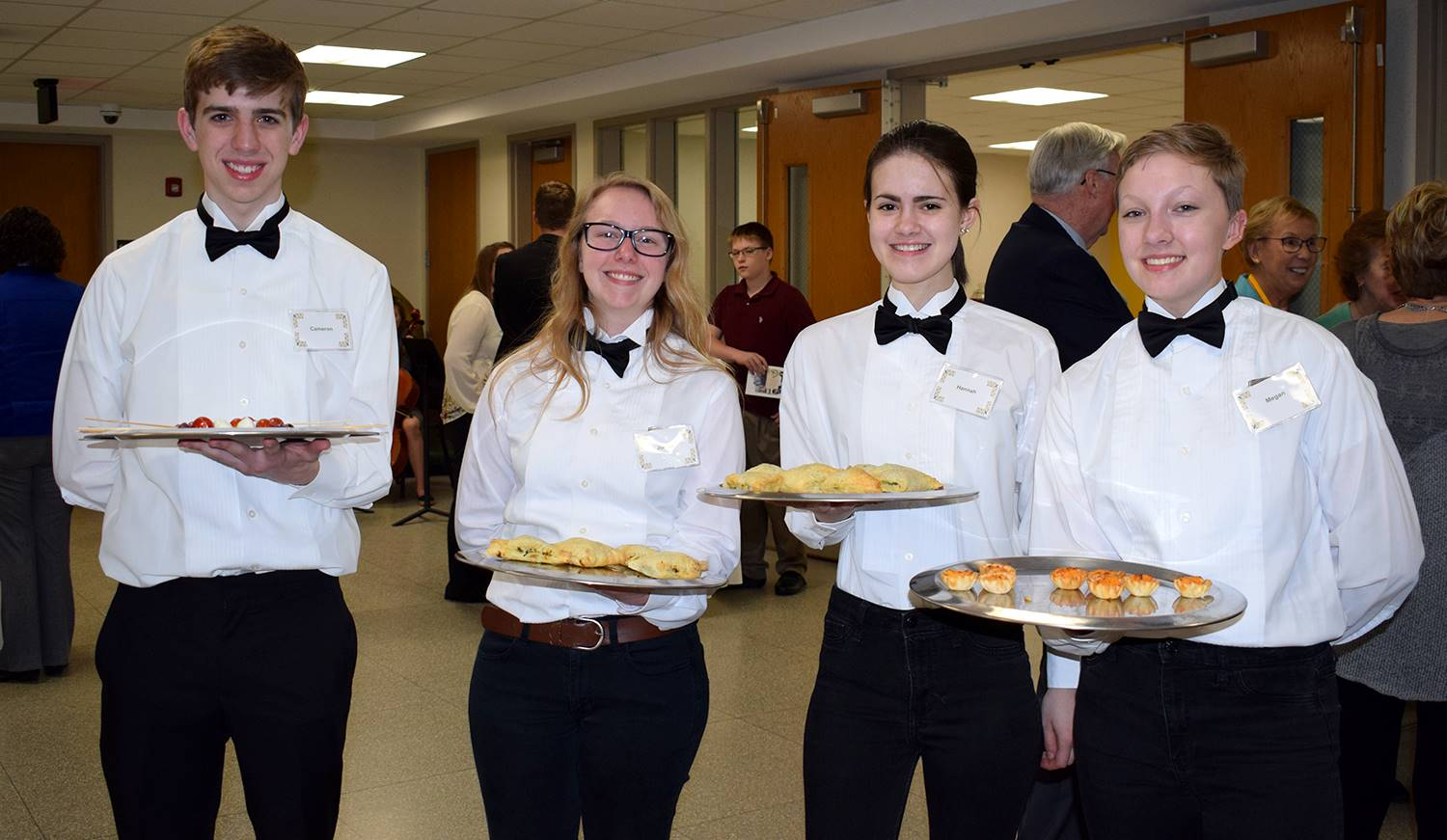 Dressed in white shirts with black bow ties and black slacks, sudent waitstaff cheerfully offer appe