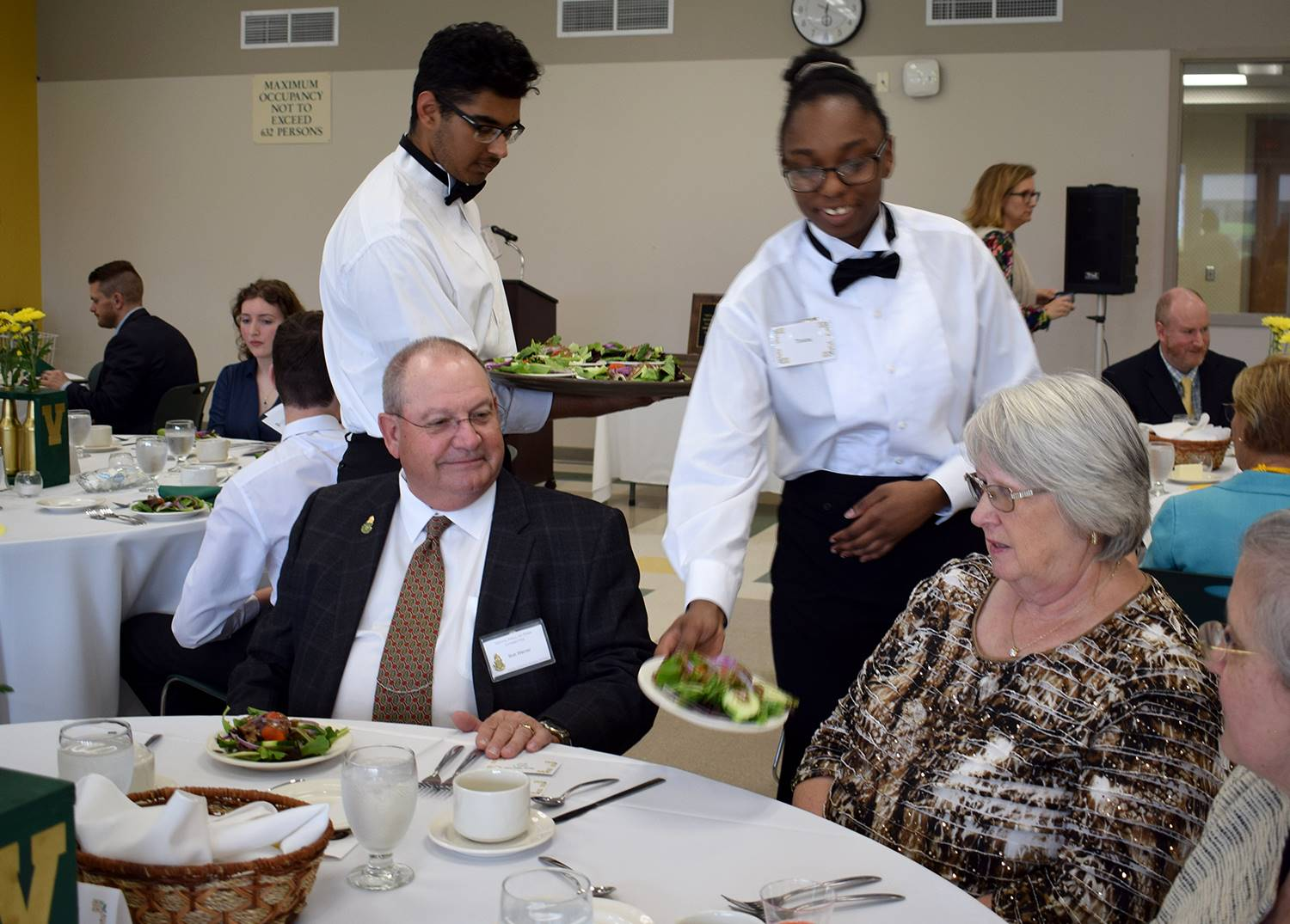 Two student waiters serve guests at the Vestal Hall of Fame Dinner on May 1, 2019.