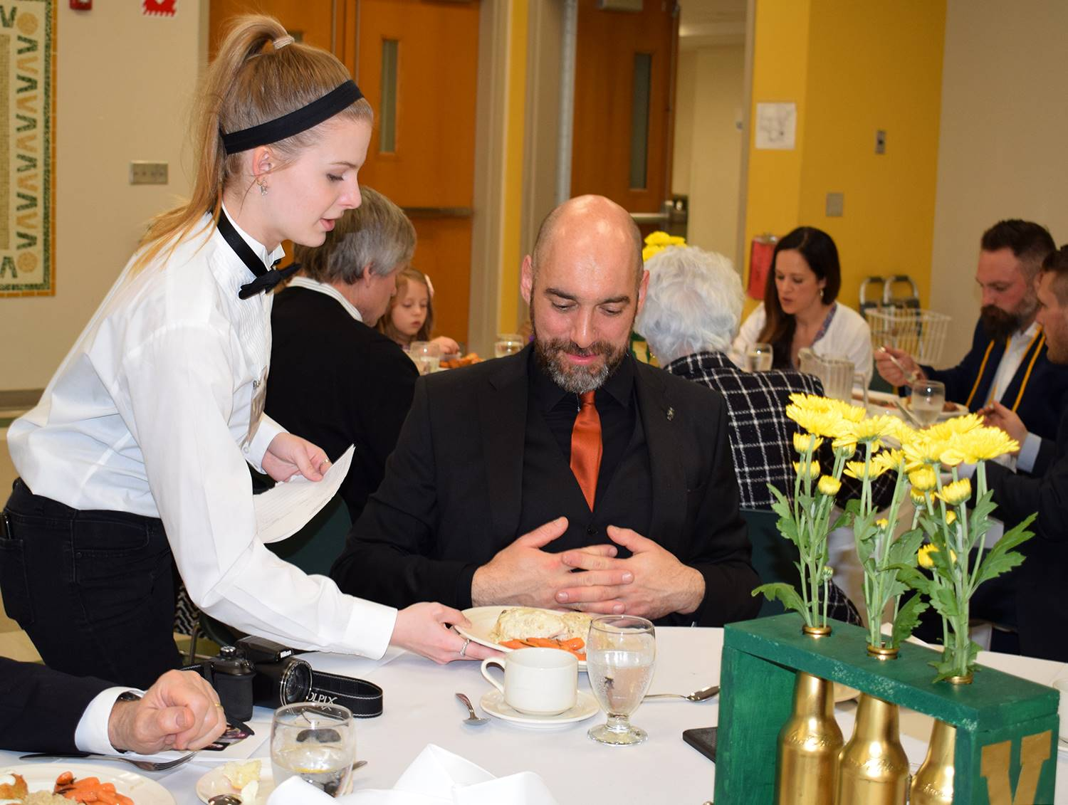 A student waitress serves Mr. Hadsell his dinner entree.