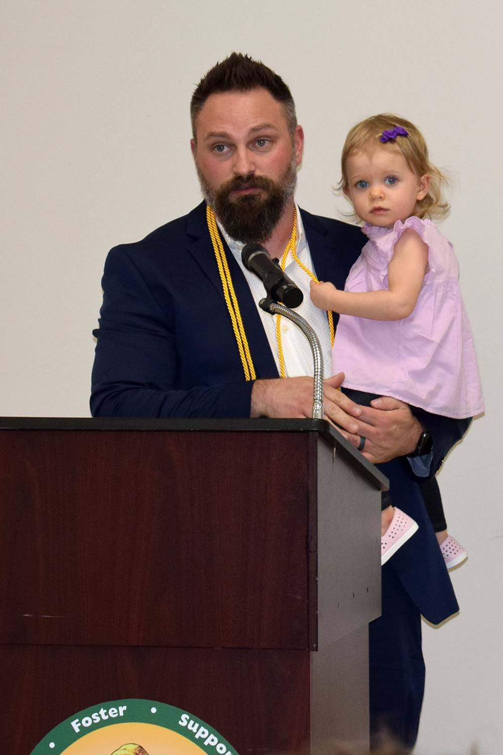 Mr. Jared Campbell at the podium, holding his youngest daughter as he gives his acceptance speech.