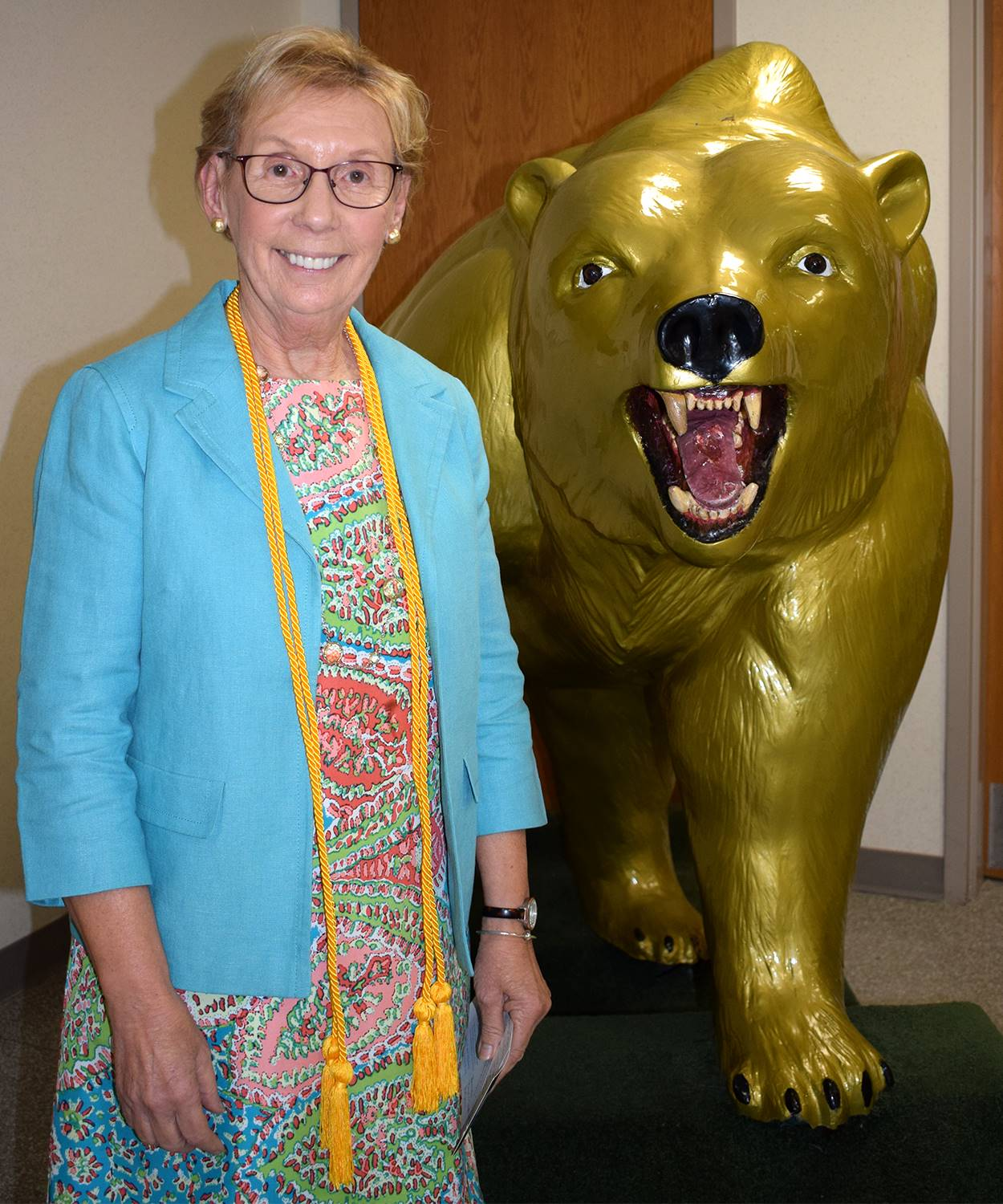 Mrs. Thea Benzelewski Prettyman next to the Vestal Golden Bear in the Vestal High School lobby.
