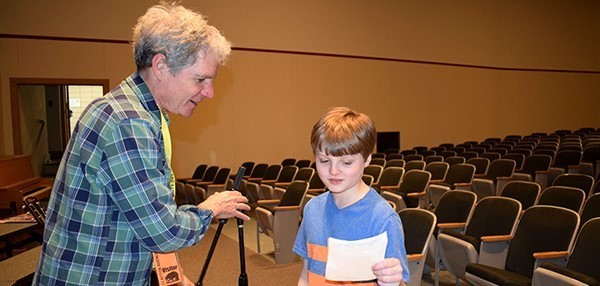 Musician David Ruch reads a poem written by a Clayton Avenue Elementary School boy after his presentation on the music and lifestyle of workers on the Erie Canal. In the Clayton Avenue Auditorium on May 21, 2019.