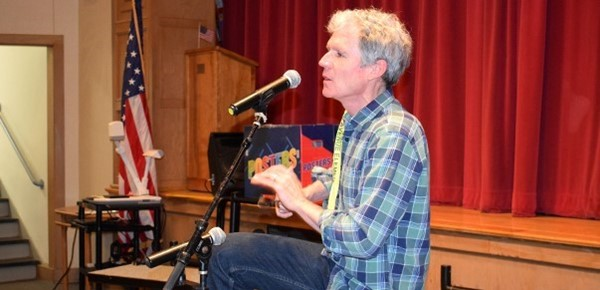 Erie Canal presenter and musician David Ruch plays the spoons in the Clayton Avenue Elementary Auditorium during his program to students on May 21, 2019.