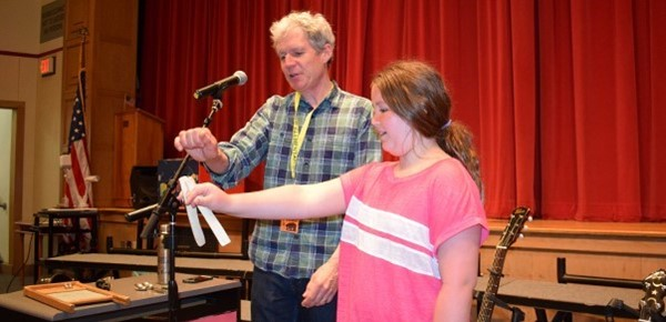Visiting musician and guest speaker David Ruch helps a Clayton Avenue Elementary School girl hold the bones to play music on; in the school's auditorium on May 21, 2019.