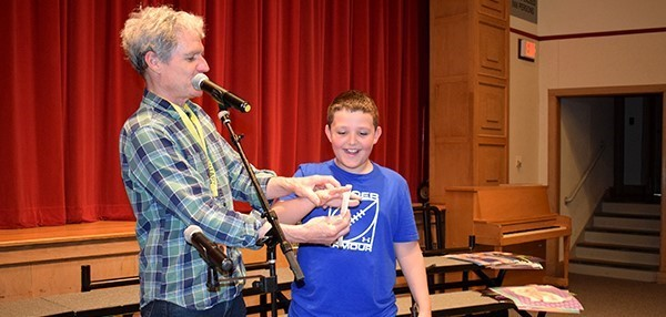 Musician and guest lecturer David Ruch shows a boy how to play the bones during a program in the Clayton Avenue Elementary Auditorium on May 21, 2019.