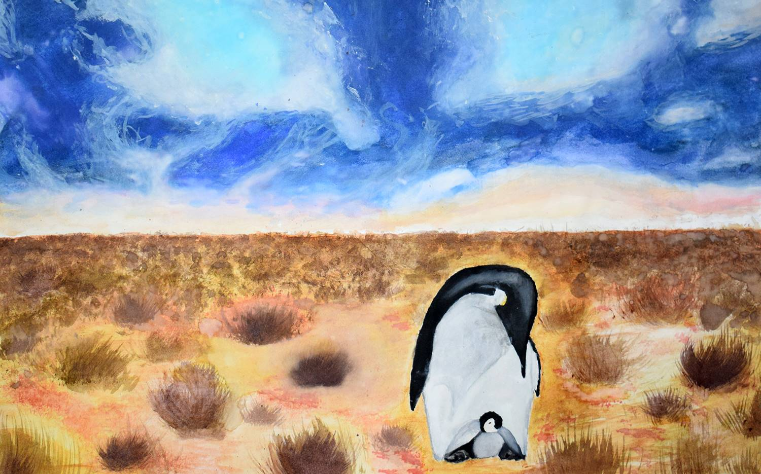 A father penguin with its baby on its feet standing in the dessert.