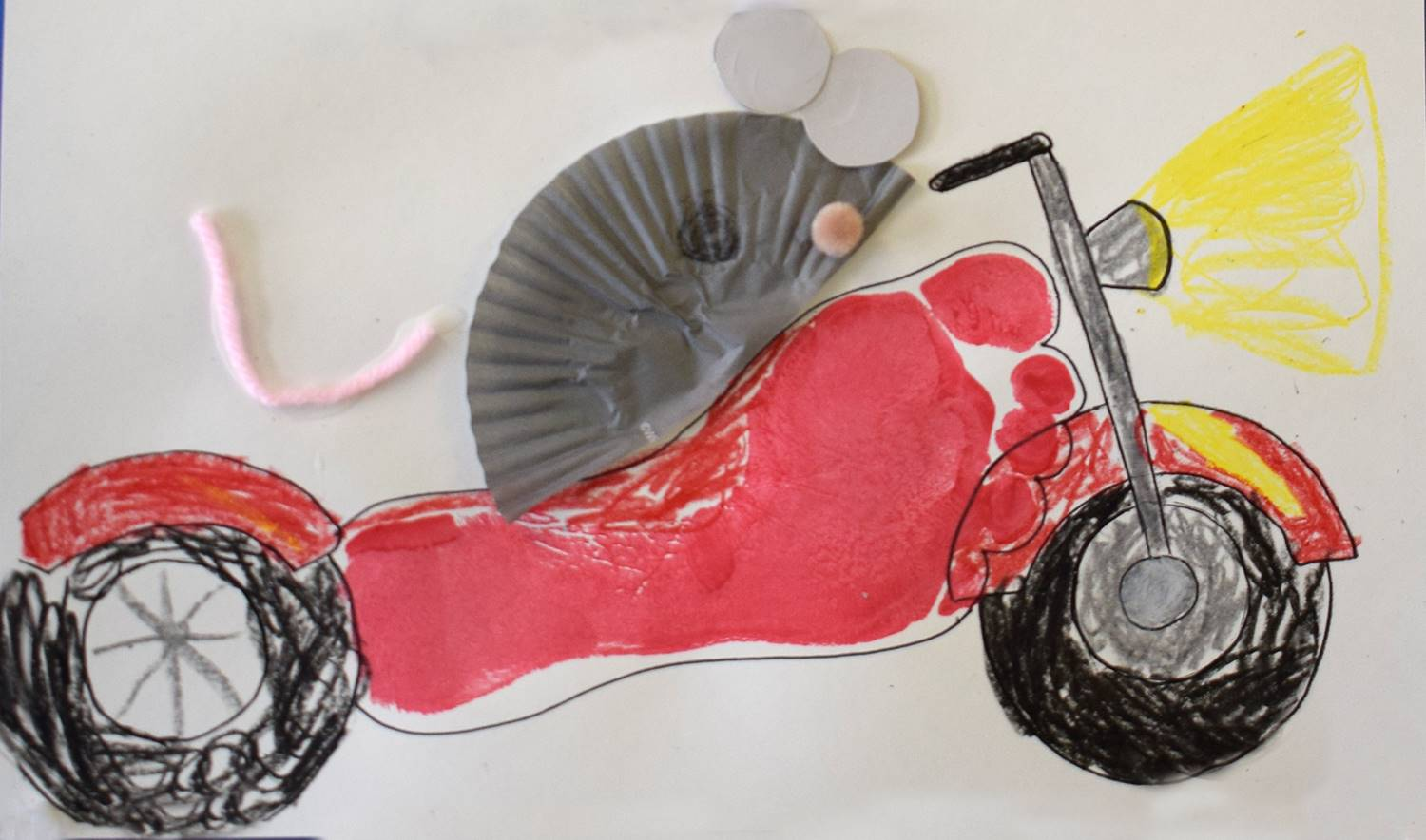 A motorcycle made with imprint of the student's foot in red paint for the body and then a gray paper