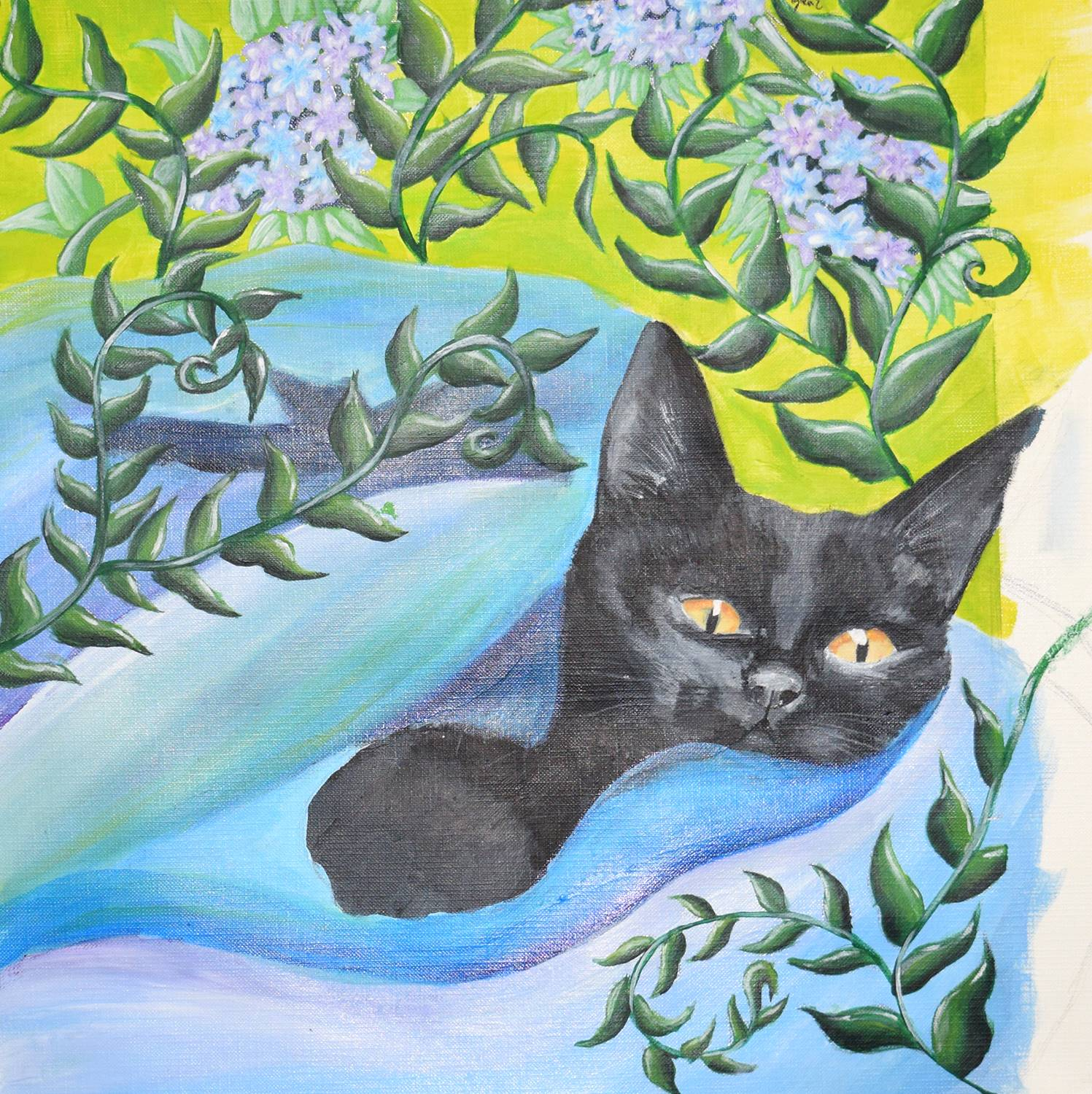 A black cat in blue blanket with lilacs around it.