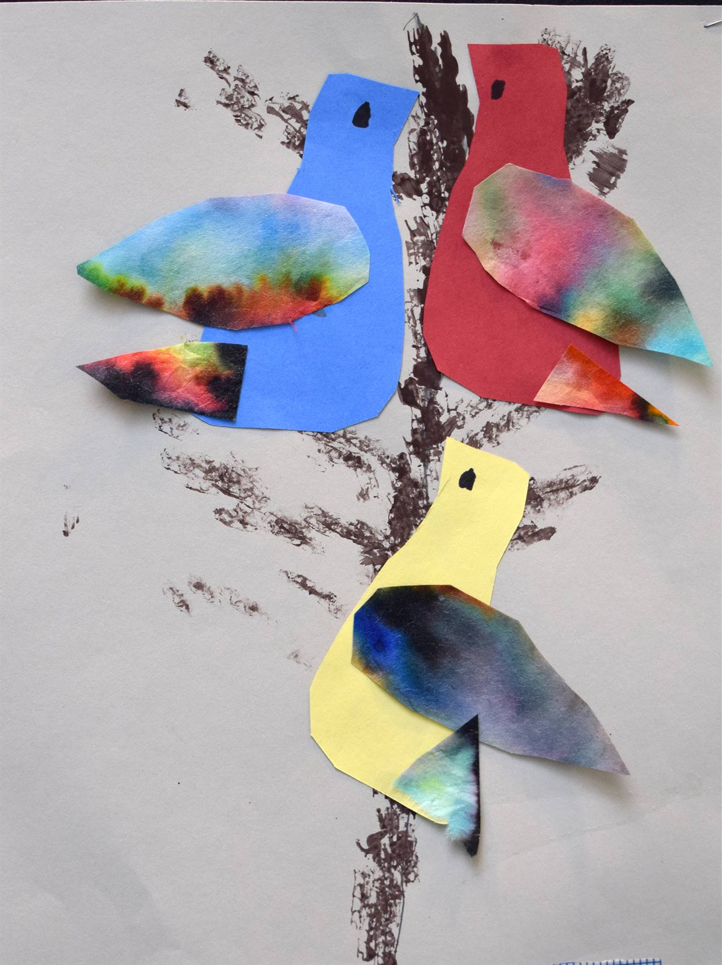 Three multi-colored birds on a black branch... One is yellow, one is blue and one is red. All have t