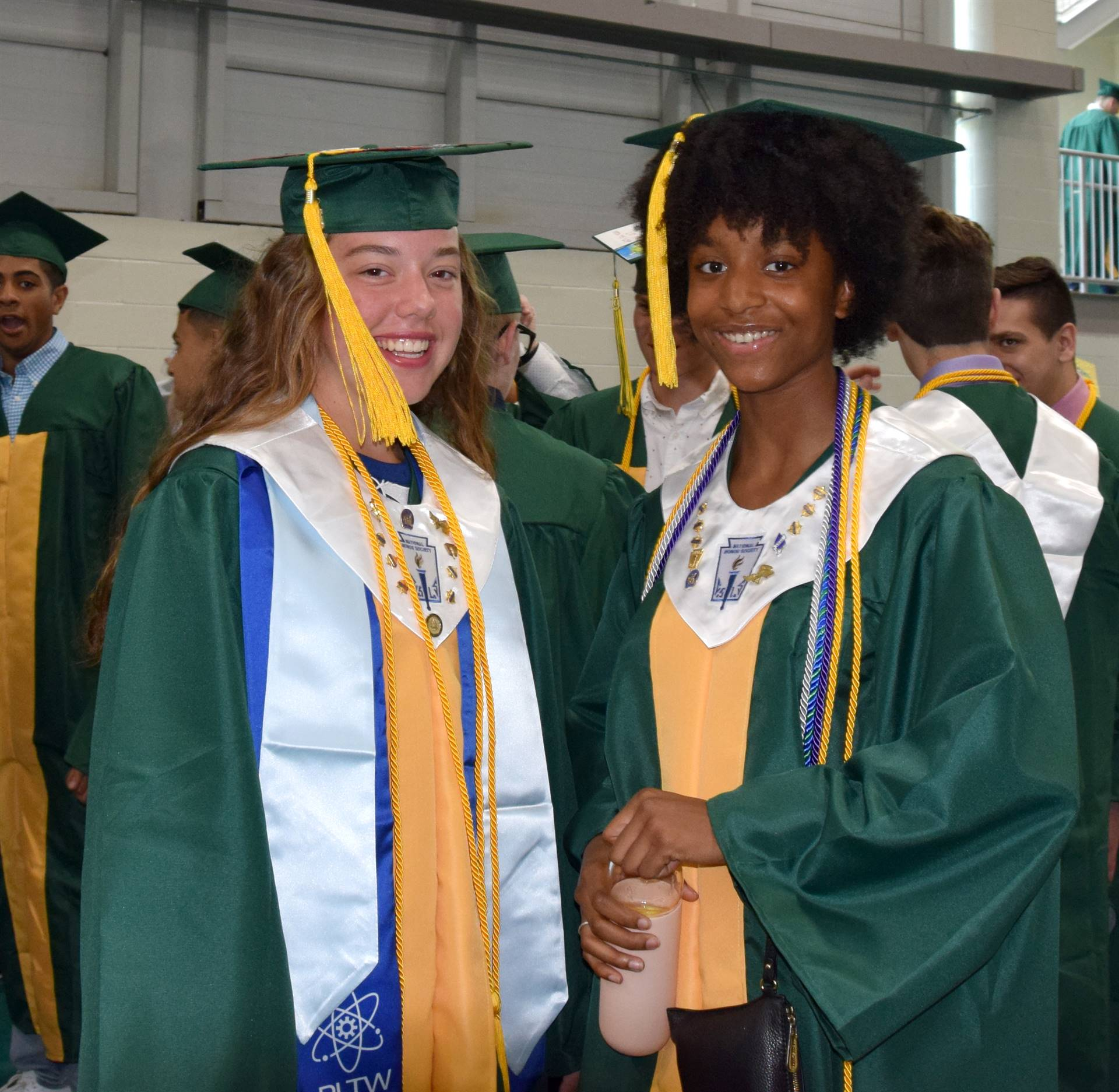 Two girls in green caps and gowns chat before their Vestal High School graduation on June 29, 2019.