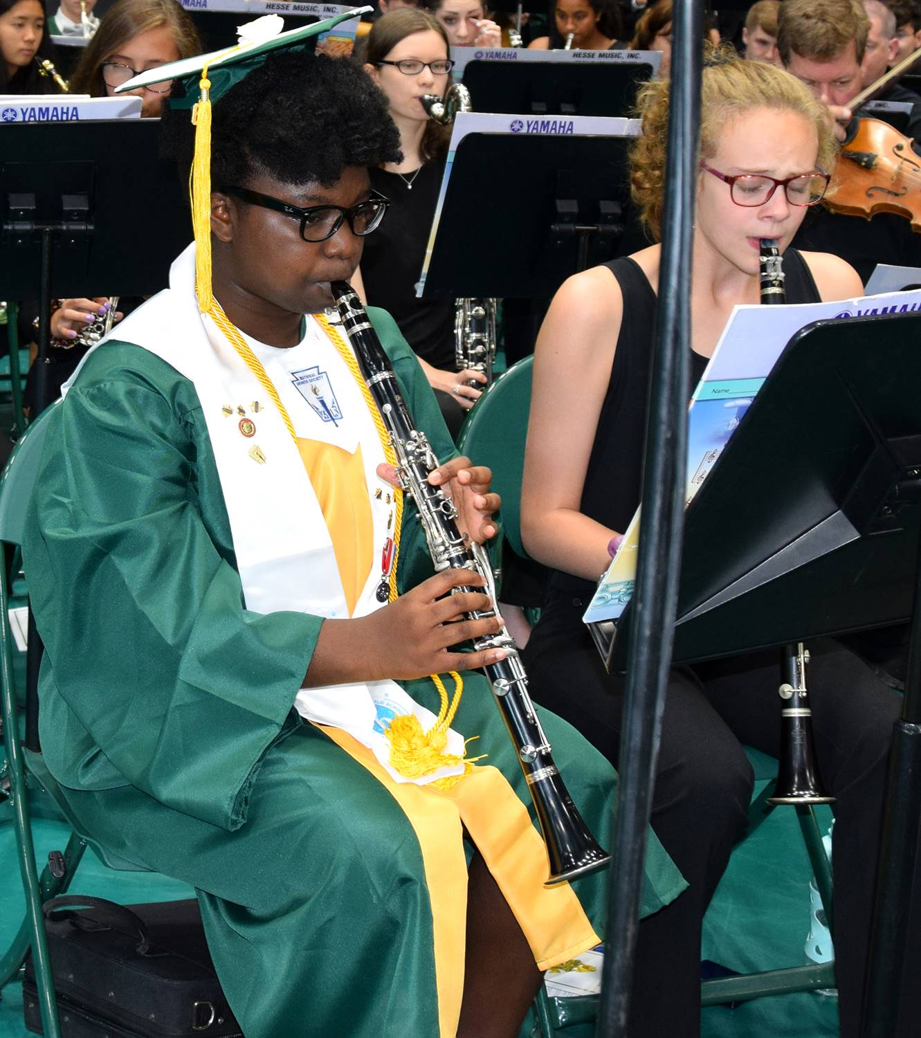 A girl in green cap and gown plays in her own Graduation Band on the floor of the Binghamton Univers