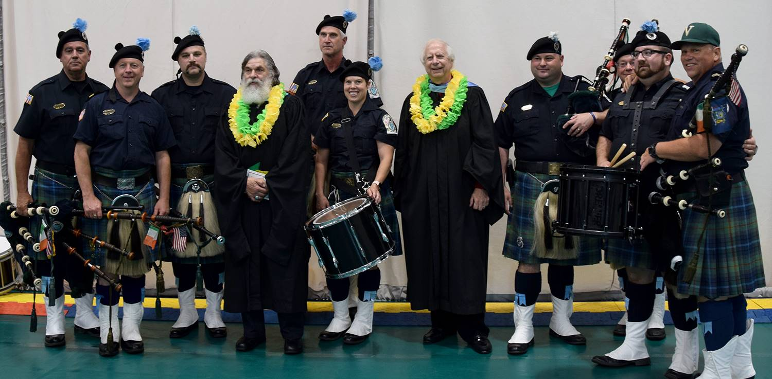 Two Board members in black robes with green and yellow leis around their necks pose for a photo with