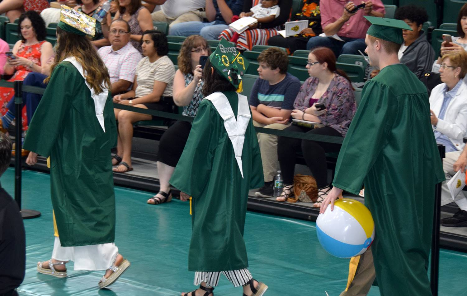 Three Vestal High School candidates for graduation process onto the Events Center floor, and one is
