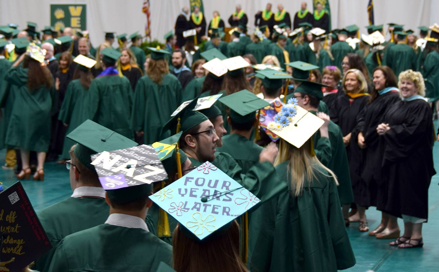 Teachers greet the graduation candidates as they enter the floor of the Events Center to take their