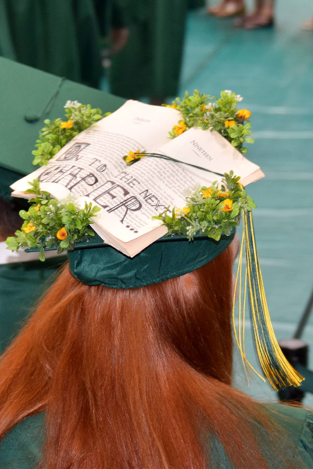 A girl with long red hair seats in her seat for graduation, her mortarboard decorated with an open b