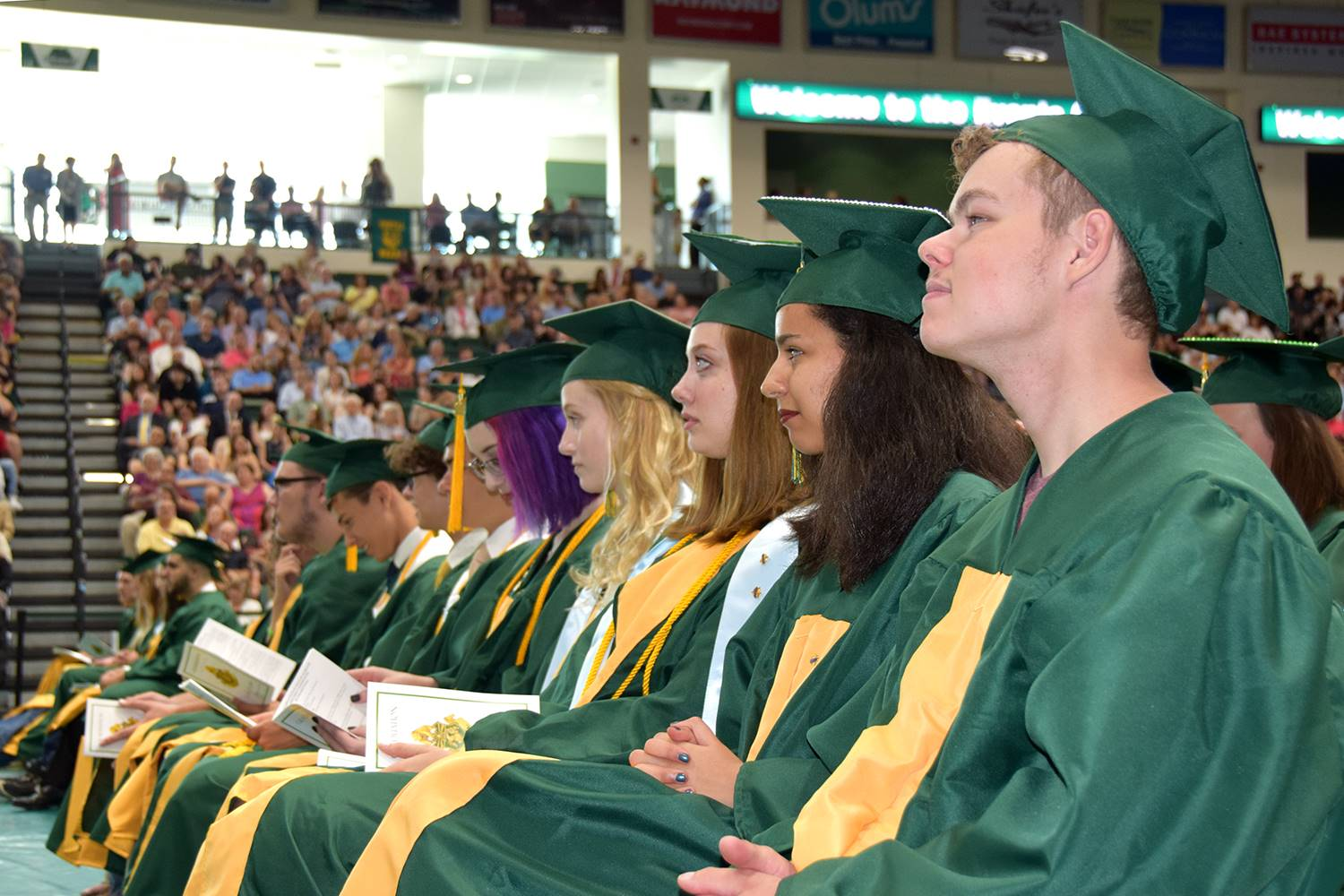 Graduation candidates in the front row listen respectively to their Valedictorian during his graduat