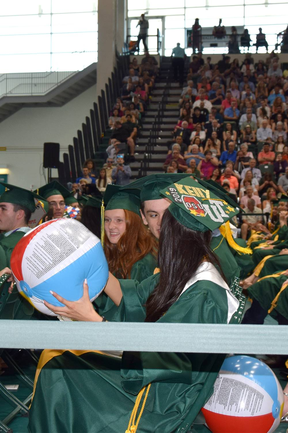 A Vestal High School graduation candidate holds a red, white and blue beach ball, ready to toss it.