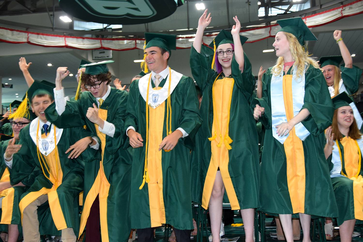 Graduates-to-be in the front row stand up after another Vestal High School Graduation tradition, the