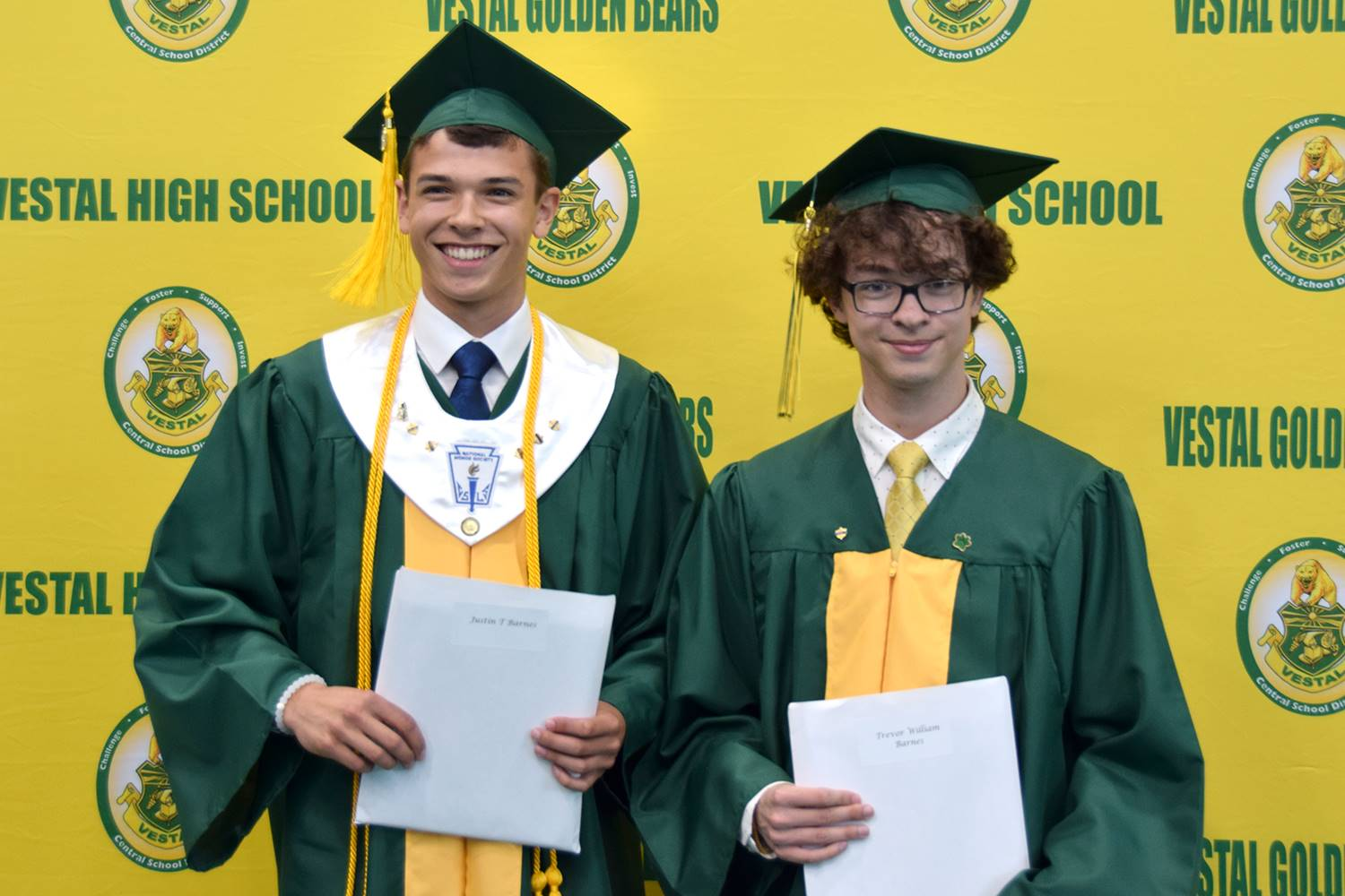 Two brothers, Vestal High School graduates stand in front of the yellow and green wall holding their