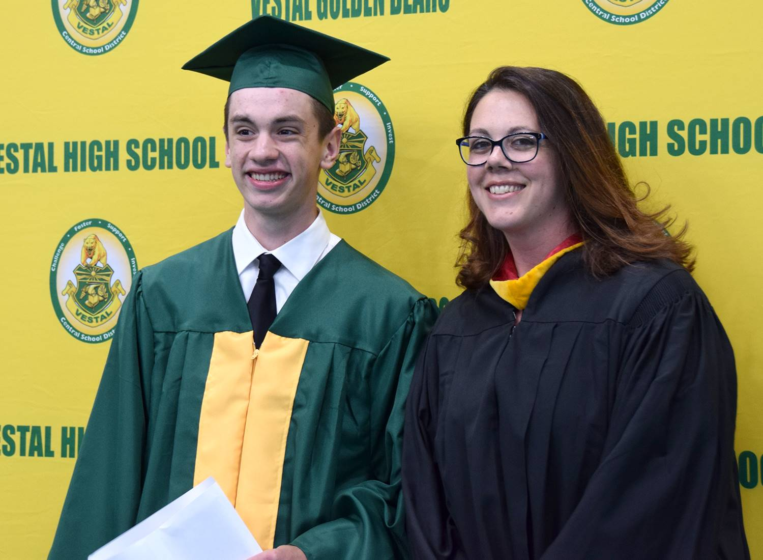 A Vestal High School graduate stands in front of the yellow and green wall with his aunt, a Vestal t
