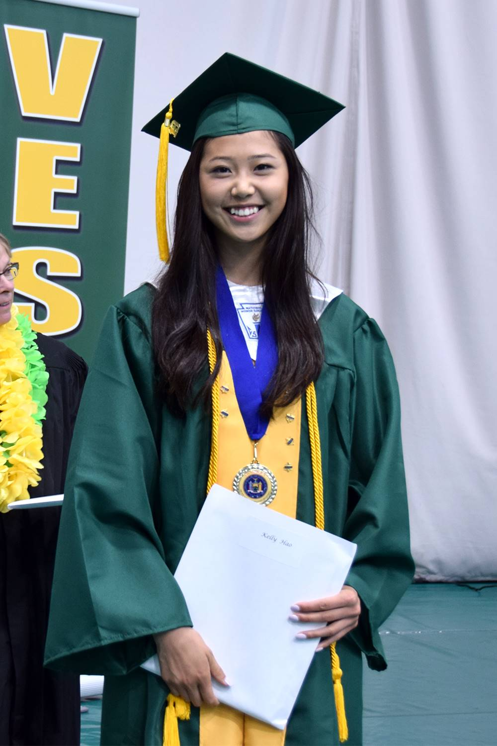 A graduate stands with her diploma after receiving it.