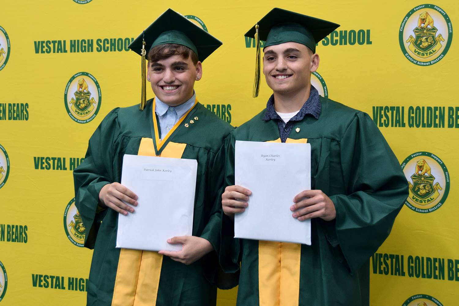 Brother Patrick and Ryan Kerley stand side by side with their diplomas in front of the yellow and gr