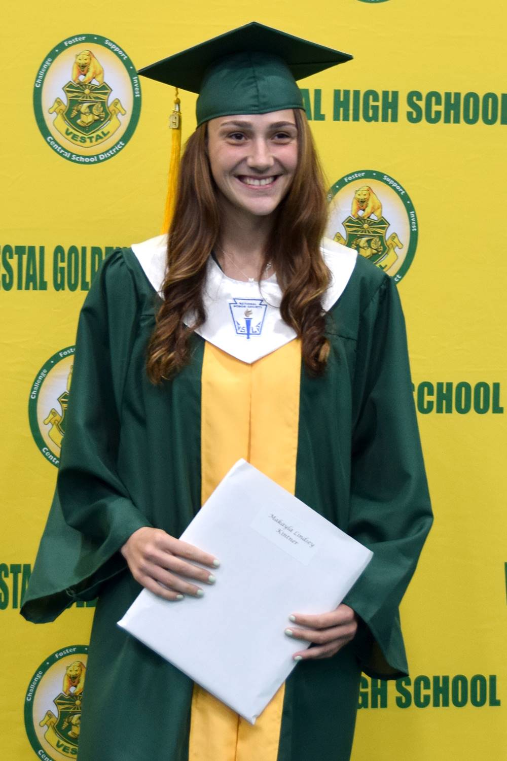 A Vestal High School graduate stands in front of the yellow and green wall holding her diploma durin