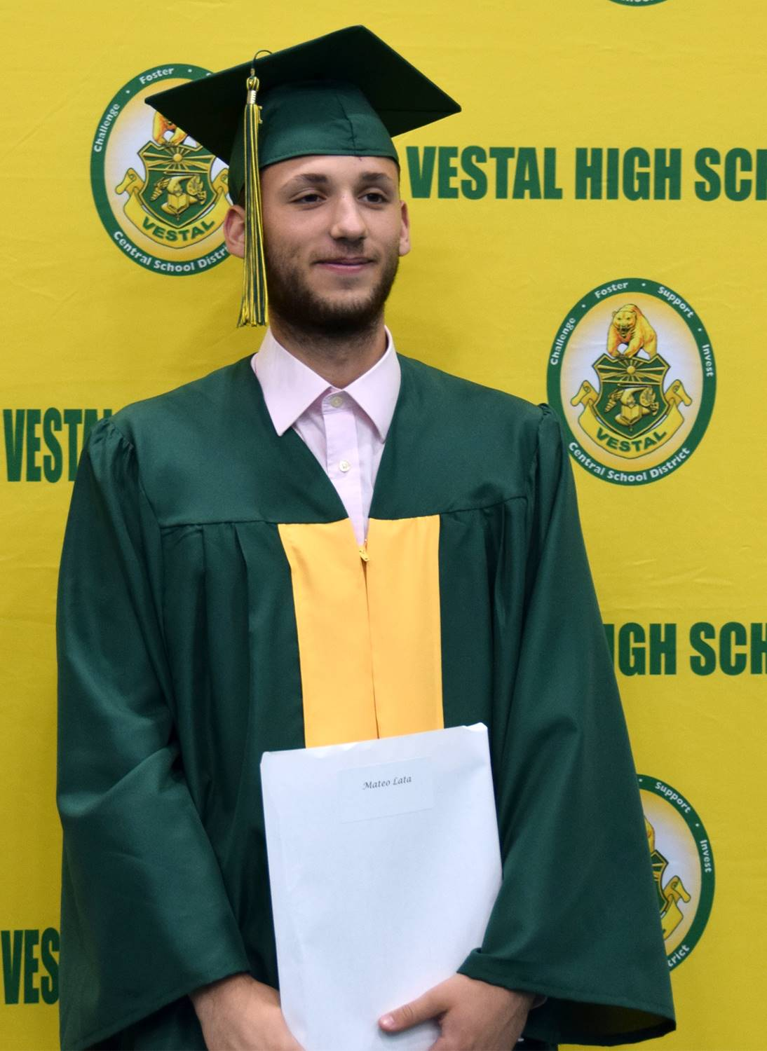 A Vestal High School graduate stands in front of the yellow and green wall holding his diploma durin