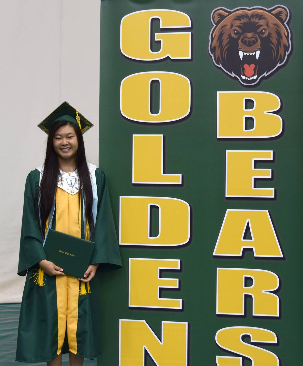 A graduate holds her diploma as she stands next to the Golden Bears sign after her Vestal High Schoo