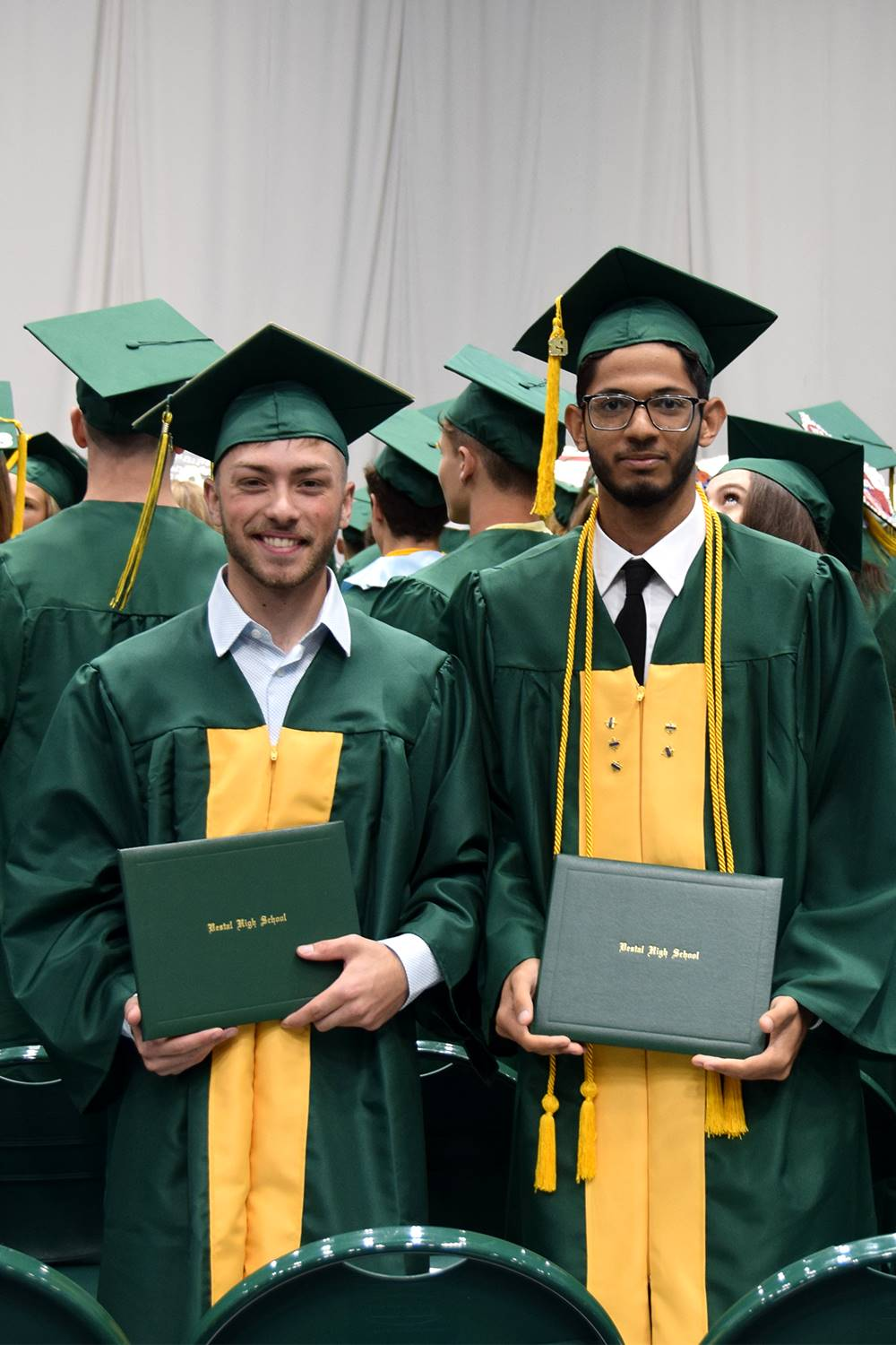 Two Vestal High School graduates hold their green diplomas before they take their seats again.
