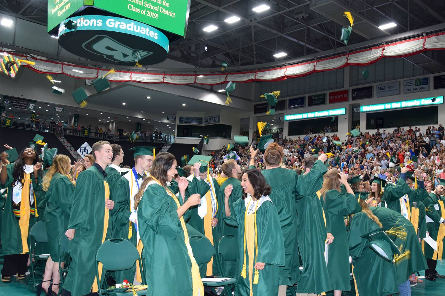 Vestal High School graduates toss their caps in the air after their graduation ceremony on June 29,