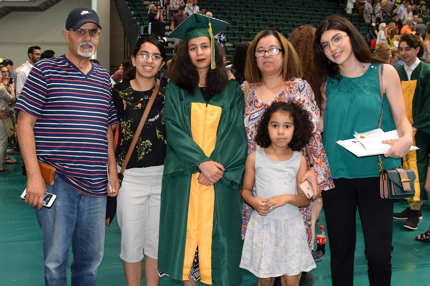 Another graduate stands for a family photo with her parents and three sisters after her Vestal High
