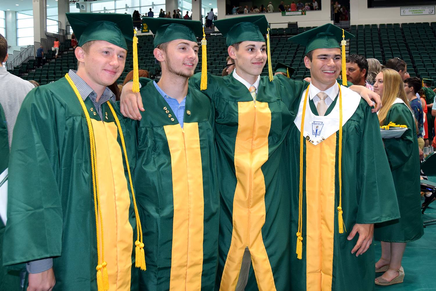 Four guys in green caps and gowns stand together for a group photo after their Vestal High School gr