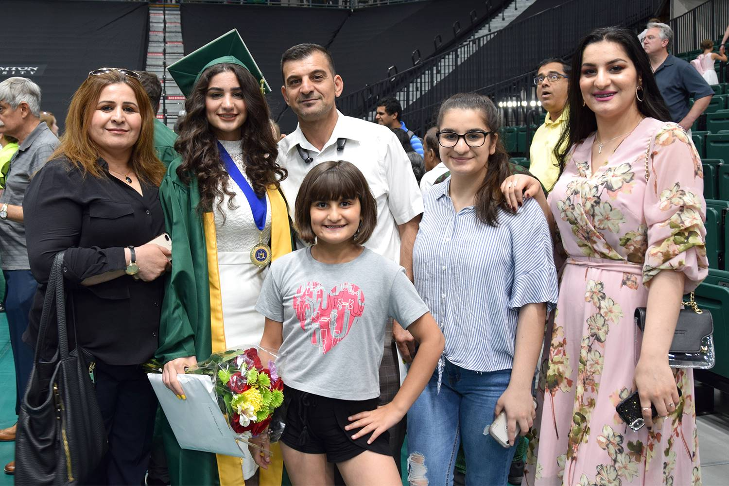 A large family of two parents and three sisters pose for a photo with their Vestal High School gradu