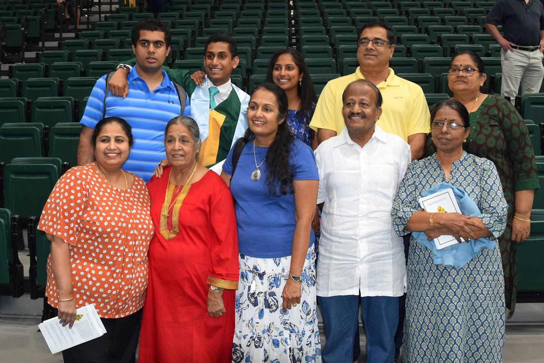 A graduate stands behind his parents, grandparents siblings and aunts and uncles after his Vestal Hi
