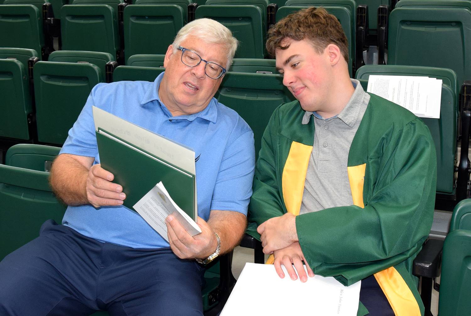 A Vestal High School graduate as he sits next to a male family member holding his diploma after his