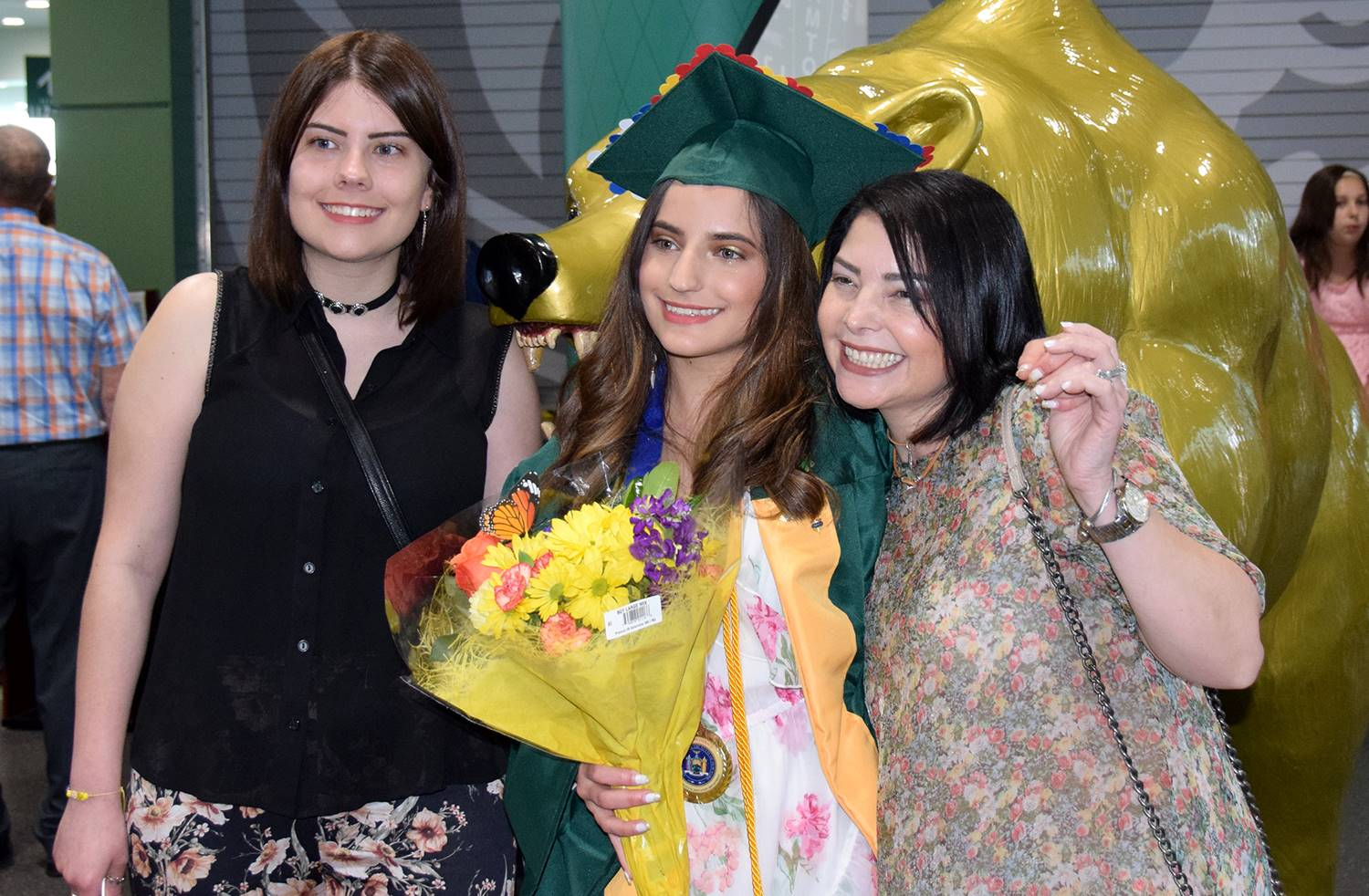 A Vestal High School graduate, her sister and mother stand in front of the Vestal Golden Bear statue