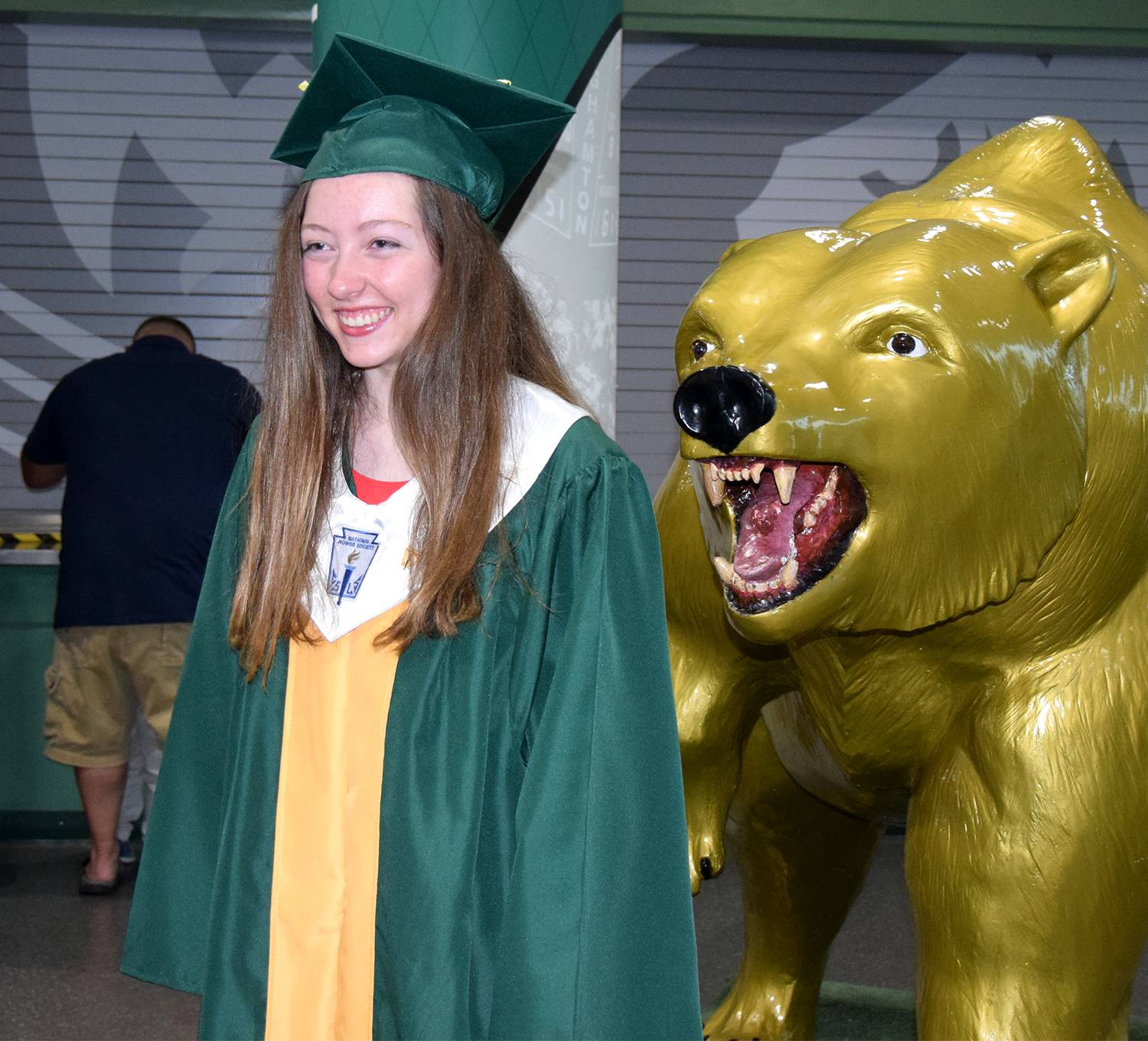 A girl smiles as she stands in front of the Vestal Golden Bear statue after her Vestal High School g
